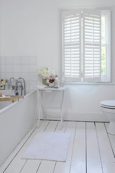 Wooden floorboards are painted white to match the rest of the scheme, but the montage of green photo frames and vase of flowers add a hint of colour to ensure the space feels light and fresh rather than washed out. Painted Bathroom Floors, Painted Floorboards, White Floorboards, Wood Floor Bathroom, Bathroom Flooring, Tile Floor, Parquet Flooring, Bathroom Cabinets, Wood Paneling
