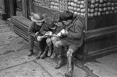 Children eating apples as they read a comic outside a shop, one little boy is wearing a tin-hat Bert Hardy
