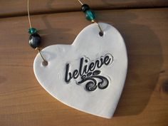 "The beautiful swirl design accents the word ""believe"" in black glaze over a white background.Hung from heavy duty wire and accented with black and teal glass artisan beads,"