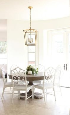 Round gray wash dining table in a bright white dining room surrounding white walls in Benjamin Moore Simply White.