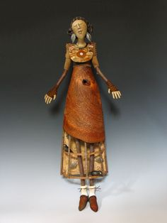 """""""Devotion"""" - Akira Blount (materials: cloth: needle sculpted, iron oxide transfer; flax paper over cloth face and hands; turned, carved Cherry skirt; Grape vine hoops, Poplar branch arms and legs, (2) air dry clay birds, leather leaves, wire, beads, plywood and paper back, colored pencil, acrylic paint, metallic rubs)"""