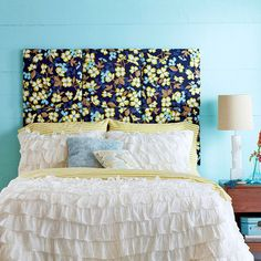 To create this unique bedroom focal point, we cut plywood into 18-inch squares and folded cotton batting over each, stapling the material in place. For each square, a larger piece of floral fabric was cut (allow for at least 2 inches of overage on each side) and stretched over the front, around to the back, and stapled in place.