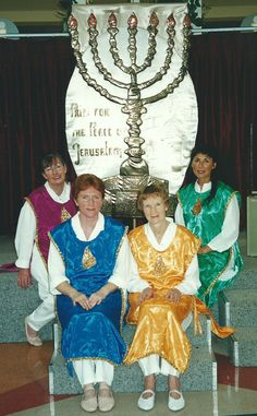 Rosalyn Glenys, Ella and Rita dressed in Israeli Folk Dance costumes, photographed under the Pray for the Peace of Jerusalem Banner at Coastlands, Paraparaumu, New Zealand in 2000...