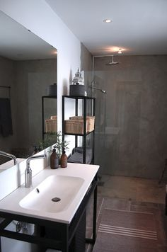 Stylish, modern bathroom that makes good use of and striking black metal and dark grey tile.