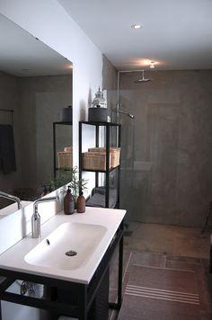 Stylish, modern bathroom that makes good use of and striking black metal and dark grey tile.