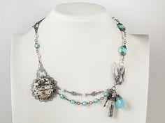 Steampunk Necklace bird bottle and blue crystal on display #steampunkjewelry #steampunknecklace #steampunk