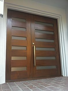 These contemporary front doors are made of mahogany and feature obscure glass with a custom stainless steel pull.