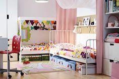 Dormitorio infantil compartido. Dos camas de IKEA colocadas en forma de L y separadas por un divisor de espacios de tela.