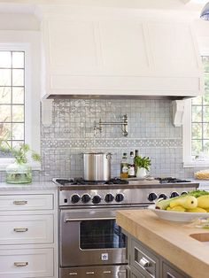 Express your personality and add a distinctive look to your kitchen with mural tiles. A band of white and blue hand-cut tiles arranged in a floral pattern divides this simple blue backsplash.
