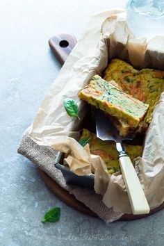 Savory Vegetable Loaf Cake~4 medium carrots, peeled 2 medium zucchini 2 medium yellow summer squash 2 Tablespoons butter or coconut oil 1 large or two small garlic cloves, finely minced ½ teaspoon sea salt divided 1/8th teaspoon ground pepper 6 large eggs ¼ cup/60ml kefir or coconut milk ¼ cup/28g coconut flour, sifted ½ teaspoon baking powder 1 small handful of fresh basil leaves, chopped (about 2 to 3 Tablespoons)