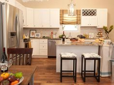 This kitchen features neutral colored walls and counter tops, white cabinetry, stainless steel appliances and a kitchen island with bar stools.