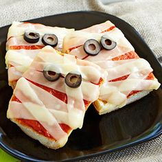 Mummy pizza: french bread, pizza sauce, strips of cheese and olives. So cute and simple
