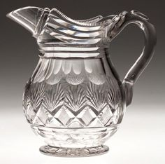 CUT STRAWBERRY DIAMOND AND FAN JUG / PITCHER, colorless, bulbous body with panels above the pattern, serrated-edge rim above the linear-cut neck, and an applied solid handle with factory cut upper thumb rest and lower terminal, raised on an applied star-cut circular foot. Probably Bakewell, Page & Bakewell, Pittsburgh. 1825-1835. 7 3/8 H, 3 7/8 W rim, 3 1/2 D foot.