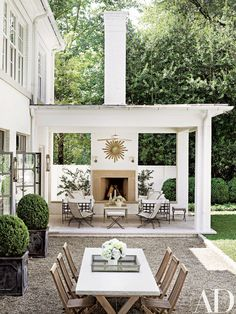 Sofas by Janus et Cie and 1950s French woven chairs from the Nicholson Gallery beckon from the terrace; the sunburst mirror is vintage.