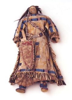SIOUX DOLL Female hide doll with horsehair hair, partially beaded hide dress, fully beaded leggings and moccasins.  Quill embroidered knife case with knife.  Illustrated in Spirits in the Art, by James A. Hanson p-131, and in Historic American Indian Dolls, by Forrest Fenn plate 37.