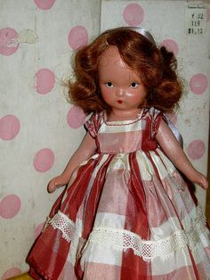 Nancy Ann. Tiny doll. She looks delightful resting in the arms of a bigger doll.
