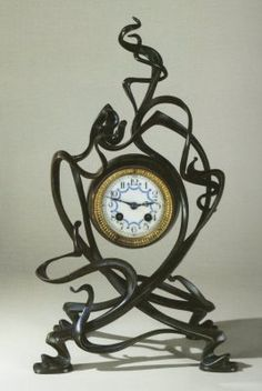 This is a Art Nouveau Clock. These Clock design was heavily influenced in the 1920s and '30s by Art Deco, a machine-like aesthetic for a fast-paced industrial age. No object escaped the streamline touch of Art Deco, including clocks, whose cases often echoed the geometric architecture of the day.