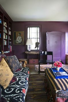 Cotton shook up the den's classic lines by coating its walls in Farrow & Ball's attention-grabbing Brinjal   domino.com
