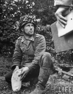 """historywars: """" A German Fallschirmjager (paratrooper) puts his belongings into a white sack after being captured by American troops during the Allied push through St. Georges D'Elle, Normandy in July 1944. """", pin by Paolo Marzioli"""