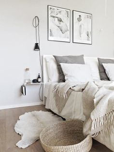 A fuzzy wool blanket, woven basket and faux hide rug bring in a natural element that boosts the cozy factor of this Scandinavian style bedroom. Colors: tan grey and black. Ivory Bedroom, White Bedroom, Modern Bedroom, Bedroom Classic, Trendy Bedroom, Scandinavian Style Bedroom, Scandinavian Bedroom, Nordic Bedroom, Scandinavian Design