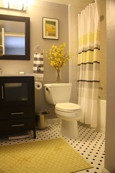 Love this bathroom's color scheme: black, grey and yellow. Also. love the vase of flowers.