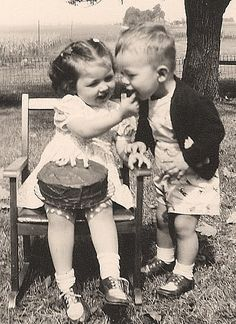 Vintage photo, circa 1950's, of a little girl sharing a dollop of icing from her birthday cake.