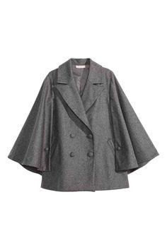 Cape en laine mélangée: Cape en feutre de laine mélangée. Modèle avec double boutonnage et larges revers en pointe. Fermeture par boutons habillés sur les côtés. Poches latérales passepoilées. Doublée.