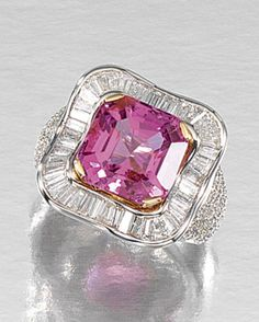 SPINEL AND DIAMOND RING.  Centring on a cut-cornered step-cut spinel within radiating surrounds of baguette diamonds, to shoulders pavé-set with brilliant-cut stones