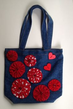 This whimsical denim tote features a variety of red polka dot hand sewn yo-yo flowers with red button centers. The bag is also accented with 2 novelty