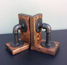 """Industrial Pipe Book Ends (pair). Constructed of ½"""" iron pipe with a CUSTOM finish mounted on wood supports. This industrial pipe set of bookends is an excellent industrial accent for your home or office. Dimensions: 6 Tall x 5"""" Width Our products are hand-crafted with a careful eye to detail. As well, we pride ourselves on the presentation of the product—the coolness effect. Every metal component is thoroughly cleaned and prepped. Finished pieces receive 2 coats of primer and paint as"""