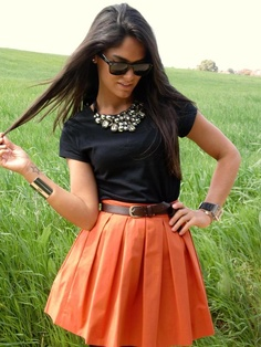 Black top, orange skirt, brown belt and chunky necklace.
