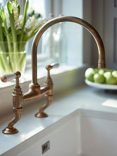 Traditional antique brass kitchen faucet with dual levers with undermount butlers sink and Carrara marble-effect composite worktop.