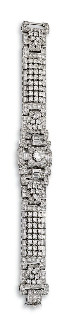 DIAMOND BRACELET, 1930S.  The articulated band of open work geometric design, set with circular-, brilliant- and single-cut, tapered baguette and baguette diamonds, mounted in platinum, length approximately 185mm, French assay marks, one diamond deficient.