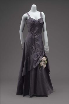 Evening dress 1942 Evening dress of navy blue silk. Bodice with narrow straps over the shoulders. Long skirt flared form the waist, with wide ruffle applied low at side-backs and curving higher in front. At highest point of ruffle a silk bow and a cluster of five aritficial roses in pale pink and lavender are attached.
