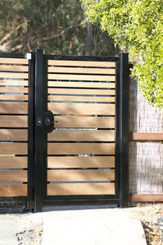 black metal gate with modern cedar center panel with slats of varying widths