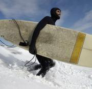 Un hombre se dispone a practicar surf en la playa de Rockaway cubierta de nieve, en Nueva York.