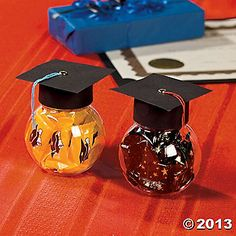 """Graduation Cap Favors Make every table at your graduation party look a little smarter when you set out these Graduation Cap Favors for your guests. Filled with treats and looking collegiate in their mortarboards these favors will be a favorite.  1. Cut a length of black paper that will wrap around the outside lid of a round storage bottle, about 1"""" wide. Glue into place.  2. Cut a square shape from a black piece of paper, about 3""""X3"""". Place a gold brad in the center of the square. 3. Cut a l..."""