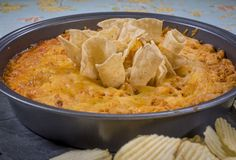 Serves 8 Ingredients  1 (8 oz.) package cream cheese, room temperature 2 cups cooked chicken, shredded 1 1/2 cups assorted cheeses (cheddar and monterey), shredded 1 cup buffalo sauce, divided 2/3 cup ranch dressing 1/2 cup sour cream tortilla chips, as needed  Directions