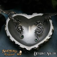 Alchemy Gothic E286 Bestia Regalis Earrings  A pair of pewter dragon stud earrings articulated at the wing joint and with emerald green Swarovski crystals; surgical steel ear-posts behind the wings.