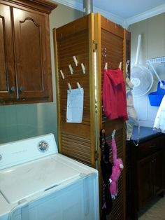 Old bifold doors in laundry room to hide water heater, provide indoor drying, and clip notes to.