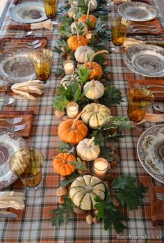 Thanksgiving table with assorted turkey plates, plaid tablecloth and easy centerpiece with pumpkins, oak leaves, nuts and votives | homeiswheretheboa...