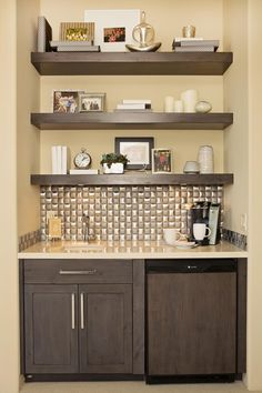 A dark wood wet bar in the master bedroom is compact and adds stylish convenience. The metallic backsplash tiles add sheen and chunky shelves provide space for accessories and keepsakes.