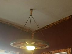 Wagon wheel light fixture with old ropes for hanging it.