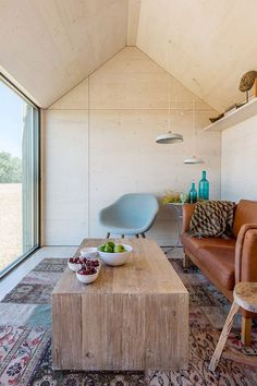 modern cabin with plywood ceiling and walls and rustic wood coffee table…