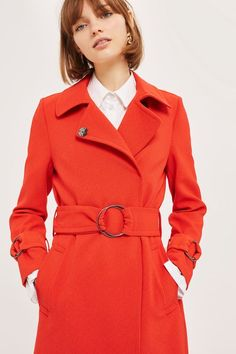 This statement red duster coat adds a pop of colour to any outfit. Metal popper fastenings down the front mean it's easy-to-wear, with the ring details on the cuff straps and belt adding a little edge to the retro shaping.