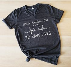 It's a beautiful day to save lives t shirt, Grey's Anatomy Tee, It's a beautiful day, Greys anatomy, Thursdays We Watch Greys Anatomy Grey's Anatomy, Greys Anatomy Tshirts, Watch Greys Anatomy, Mother Of Dragons, Vinyl Shirts, Shirts With Sayings, Custom T, Beautiful Day, V Neck T Shirt