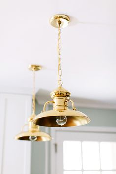 Gorgeous gold light fixtures hanging in white kitchen