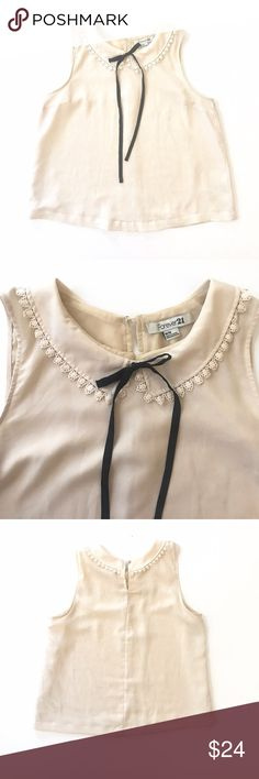 Peter Pan Collar Bow Top The prettiest cream blouse by Forever 21. It has a delicate Peter Pan collar with a black adjustable bow. Small keyhole in back. Top is lined. Size Medium. Excellent used condition.   •Lowball offers declined •no trades •ask all questions before buying •unfair ratings from buyers are reported & buyer will be blocked - I don't misrepresent my products; what you see is exactly what you get & my prices are way more than fair. Please be kind as I always strive to be kind…