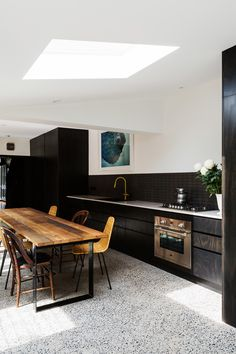 white terrazzo floor contrasts with black kitchen cabinets and stained wood furn. - white terrazzo floor contrasts with black kitchen cabinets and stained wood furniture - Kitchen 2016, New Kitchen, Kitchen Dining, Brass Kitchen, Kitchen Black, Terrazzo Flooring, Kitchen Flooring, Concrete Floors, Grey Kitchens