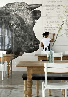 """All available space at walls to have large graphics of cows and like. Not a super sample here """"exactly"""" however simple strong bold line work.   This animal theme should dominate the mood to create a faux farm to plate """"or"""" butcher/chop house type mood??"""